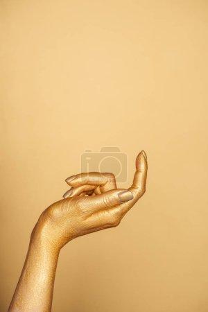 vista recortada de la mano pintada femenina aislada en oro con espacio de copia