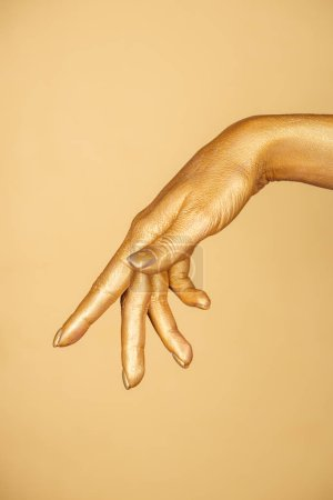 cropped view of female painted hand isolated on gold