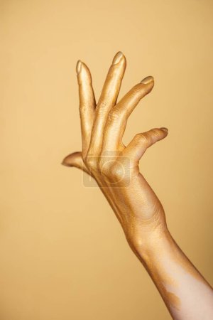 cropped view of female painted hand gesturing isolated on gold