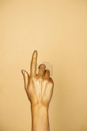 vista parcial de la mano pintada femenina aislada en oro con espacio de copia