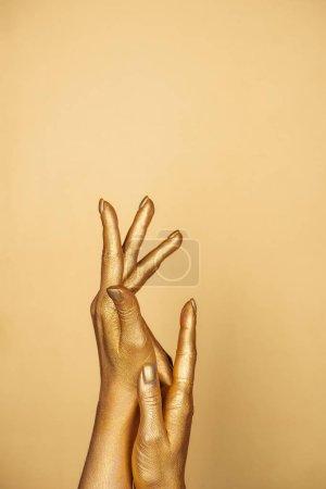 vista parcial de las manos pintadas femeninas aisladas en oro