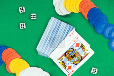 top view of green poker table and multicolored chips, dices, playing cards with diamonds suit