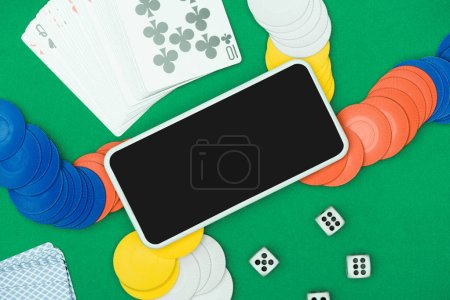 Photo for Top view of green poker table with multicolored chip, dices, playing cards  and smartphone - Royalty Free Image