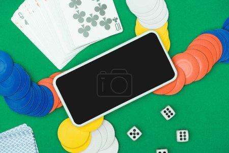 Foto de Vista superior de mesa verde con chip multicolor, dados, naipes y smartphone - Imagen libre de derechos
