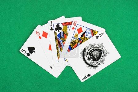 Photo pour Vue de dessus de table de poker vert avec scaphandres de carreau, pique et trèfle déplié cartes à jouer - image libre de droit