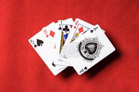 Photo pour Vue de dessus de table de poker rouge et déplié jouer aux cartes avec des couleurs différentes - image libre de droit