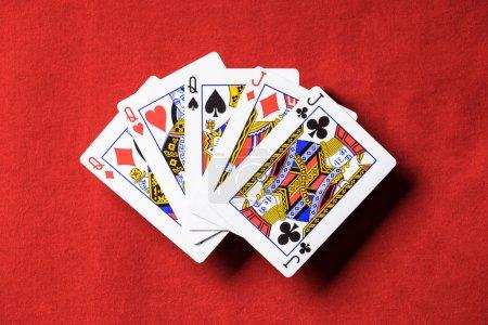 Foto de Vista superior de la mesa de poker rojo y jugando a las cartas desplegadas conjuntamente con diferentes trajes - Imagen libre de derechos
