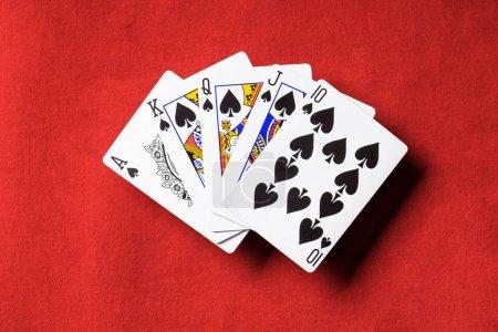 Photo pour Vue de dessus de table de poker rouge et dépliés cartes à jouer avec le costume de pique - image libre de droit