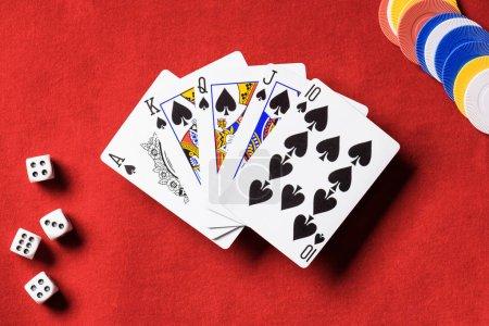Photo pour Vue de dessus de table de poker rouge et multicolores jetons, dés, dépliés cartes à jouer avec le costume de pique - image libre de droit