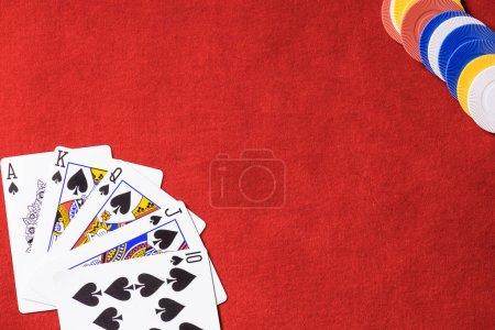 Photo pour Vue de dessus de table de poker rouge avec chips multicolores et dépliés cartes à jouer - image libre de droit