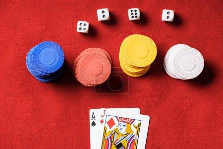 Photo pour Vue de dessus de table de poker rouge avec jetons multicolores, de dés et de deux cartes dépliées - image libre de droit
