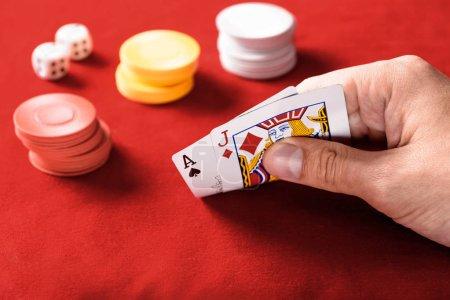 Photo pour Mise au point sélective d'homme tenant des cartes à jouer avec jetons et dés sur fond - image libre de droit