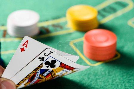Photo pour Mise au point sélective des cartes à jouer avec jetons et table de poker vert sur fond - image libre de droit