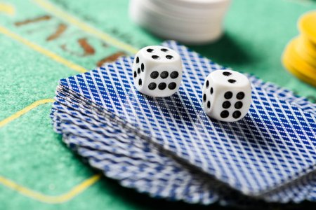 selective focus of dices on playing cards in deck with chips and green poker table on background