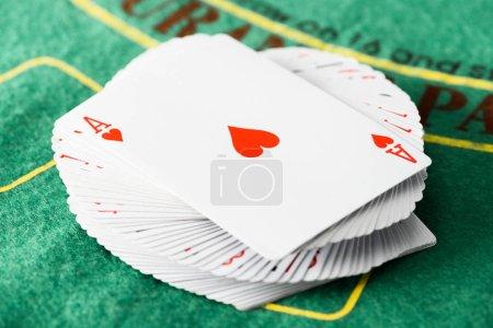 Photo pour Fonction de mise au point sélective de carte à jouer avec un cœur sur le pont à la table de poker vert - image libre de droit