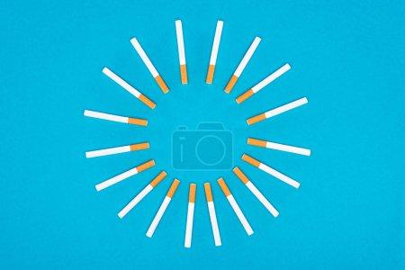 Photo pour Plat poser avec des cigarettes se situant dans le cercle isolée sur bleu - image libre de droit