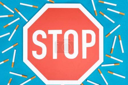 Photo pour Photo de studio de grand panneau d'arrêt avec des cigarettes isolé sur bleu, arrêter de fumer concept - image libre de droit