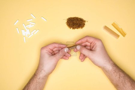 Cropped view of man making a cigarette isolated on yellow