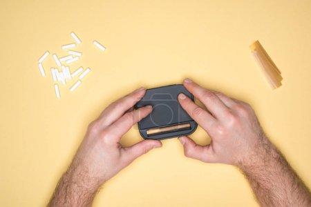 Photo pour Recadrée vue du jeune homme, rendant la cigarette isolé jaune - image libre de droit