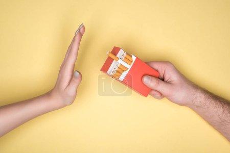 Photo pour Vue recadrée de la jeune femme refuse de cigarettes isolées sur la notion de jaune, arrêter de fumer - image libre de droit