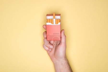 Photo for Cropped view of man holding red pack of cigarettes isolated on yellow - Royalty Free Image
