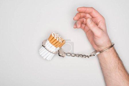 Photo pour Vue partielle de l'homme menottes aux poignets, posant avec des cigarettes isolés sur fond gris, notion de dépendance à la nicotine - image libre de droit