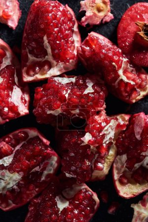 Photo for Top view of fresh cut pomegranates on black surface - Royalty Free Image
