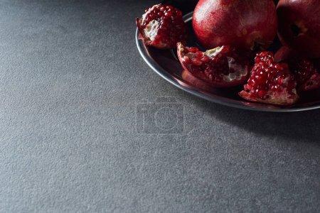 Photo pour Plan studio de grenats coupés mûrs sur assiette - image libre de droit