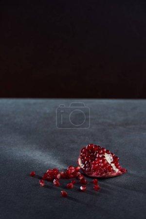 Foto de Disparo de estudio de pieza granate y semillas en la superficie oscura - Imagen libre de derechos