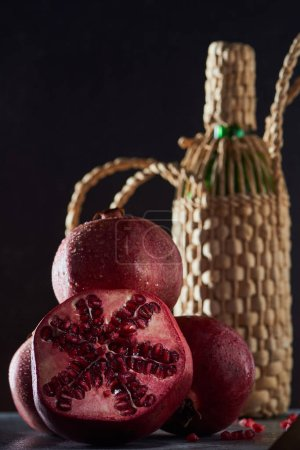 Photo for Studio shot of ripe garnets and bottle of wine - Royalty Free Image