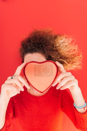 top view of girl holding heart symbol in front of face isolated on red, st valentines day concept