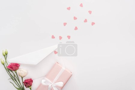 Photo pour Vue du dessus de coffret cadeau, fleurs, enveloppe et coeurs en papier isolés sur blanc - image libre de droit