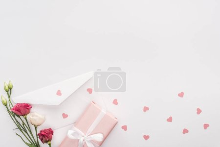 Photo for Top view of gift box, flowers, envelope and paper hearts isolated on white - Royalty Free Image