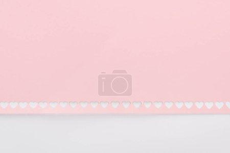 Photo pour Fond de découpe coeurs en ligne sur papier rose isolé sur blanc - image libre de droit