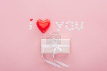 """Photo pour Vue du haut du coffret cadeau et lettrage """"je t'aime"""" en coeurs de papier isolés sur rose, concept Saint-Valentin - image libre de droit"""