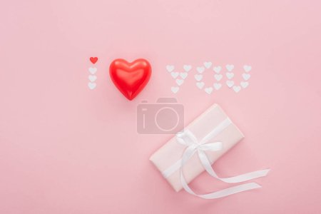 Photo for Top view of gift box and 'i love you' lettering made of paper hearts isolated on pink, st valentines day concept - Royalty Free Image