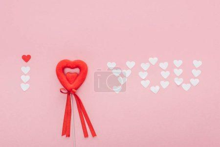 top view of 'i love you' lettering made of paper hearts and heart shaped decoration isolated on pink, st valentines day concept