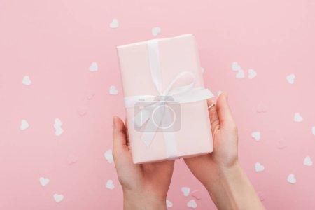 abgeschnittene Ansicht einer Frau mit Geschenkbox und Papierherzen isoliert auf rosa