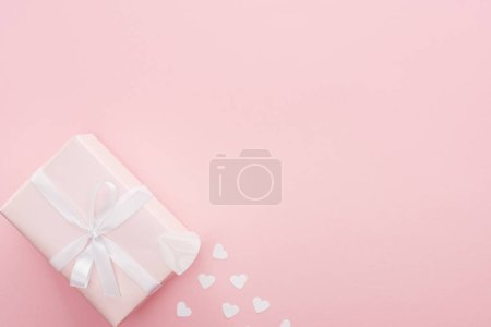 top view of gift box and paper hearts isolated on pink with copy space