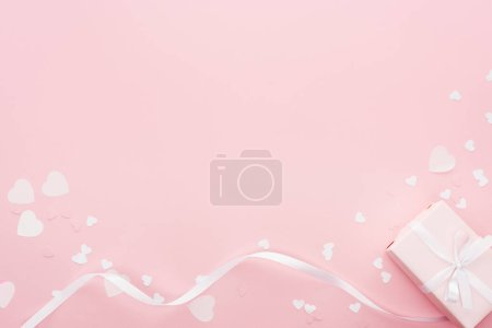 background with gift box and paper hearts isolated on pink