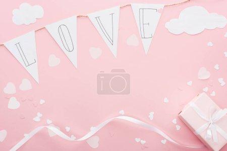 Foto de Vista superior de guirnalda de papel con 'amor' y letras la caja aislada en rosa, San Valentín concepto - Imagen libre de derechos