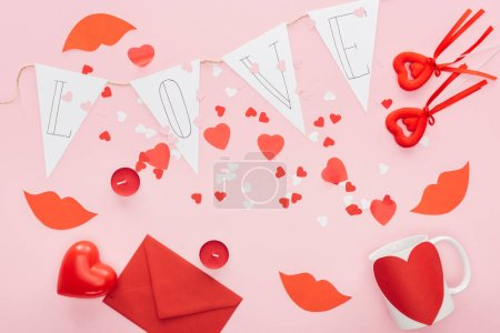 top view of valentines decorations and paper garland with 'love' lettering isolated on pink, st valentines day concept