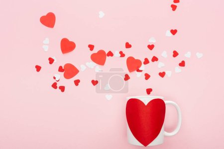 Photo for Top view of paper hearts and cup with heart shaped sticker isolated on pink, st valentines day concept - Royalty Free Image
