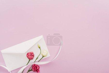 Photo pour Vue de dessus des fleurs et enveloppe isolée sur rose avec espace copie - image libre de droit