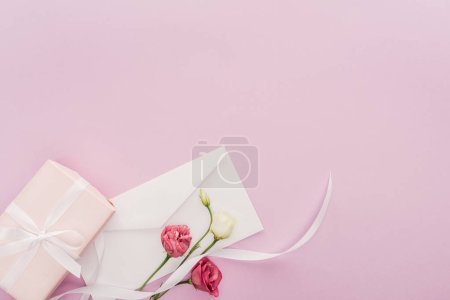 Photo for Top view of gift box, envelope and flowers isolated on pink with copy space - Royalty Free Image