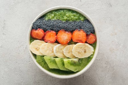 Foto de Vista superior del tazón delicioso smoothie con frutas frescas sobre fondo gris - Imagen libre de derechos