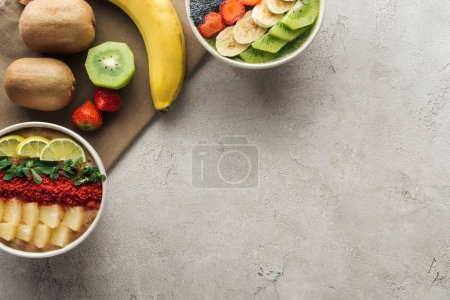 Photo for Top view of smoothie bowls with fresh fruits and organic ingredients on grey background with copy space - Royalty Free Image
