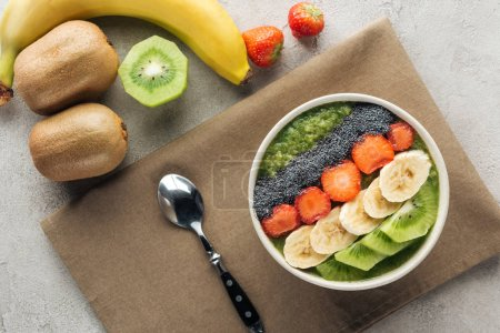 Photo for Top view of smoothie bowl with fresh fruits, spoon and ingredients on grey background - Royalty Free Image