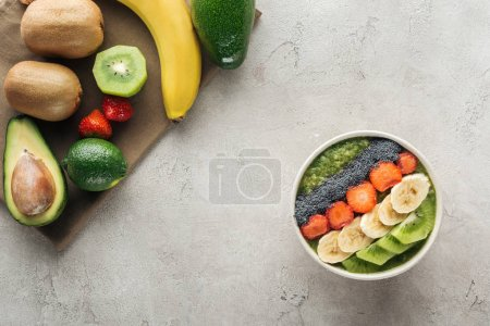 Photo for Top view of smoothie bowl with fresh fruits and ingredients on grey background with copy space - Royalty Free Image