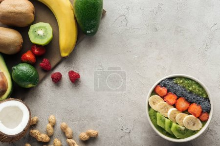 top view of smoothie bowl with fresh fruits and nuts on grey background
